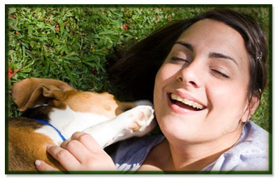 Woman laying on her fresh clean grass with her dog